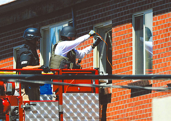 警方借助云梯试图翻窗进入霍尔姆斯的家里。