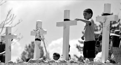 22日,少年埃玛站在悼念枪击案遇难者的十字架前。 新华社发