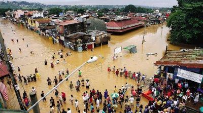 8月8日,在菲律宾首都马尼拉郊区,当地居民涉水返回洪水中的家。本版图/新华社