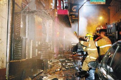 消防员在现场灭火。巴西南里奥格兰德州圣玛丽亚市中心一家夜总会27日凌晨发生火灾,目前警方已确认有245人死亡,数百人受伤。火灾发生时,夜总会正举行一场大学生聚会。警方表示,死者多因大火产生的浓烟窒息死亡,部分死者是在逃生过程中被人群踩踏而死。