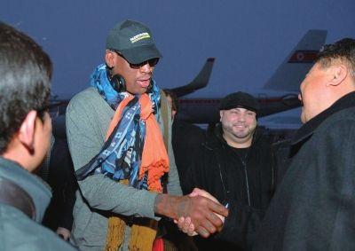 19日,前NBA球星丹尼斯・罗德曼(左二)到达平壤机场后与官员握手。新华社发