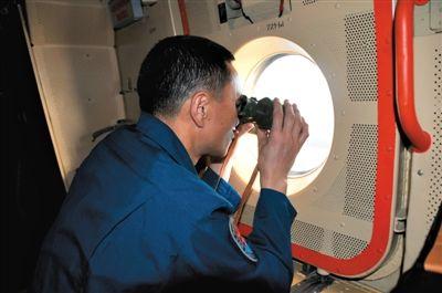 24日,中国空军机组人员在任务海域搜索。 新华社发