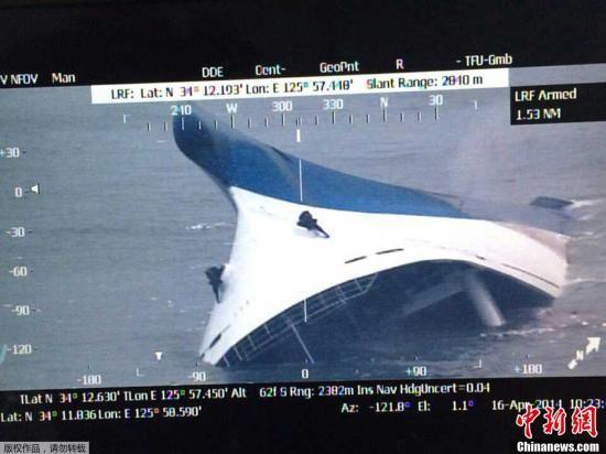"""当地时间16日上午8时58分许,一艘载有470余名乘客的""""岁月(SEWOL)号""""客轮在韩国西南海域发生浸水事故下沉。图为""""岁月号""""客轮几乎全部沉没,救援人员爬上船体进行救援。"""