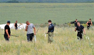 7月18日,乌克兰顿涅茨克,救援人员在飞机失事地点附近寻找遇难者遗骸。