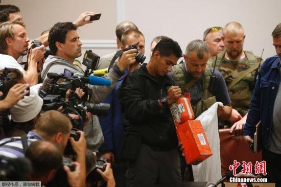 """当地时间2014年7月22日,顿涅茨克,""""顿涅茨克人民共和国""""官员向马来西亚调查人员移交马航MH17航班客机黑匣子。"""