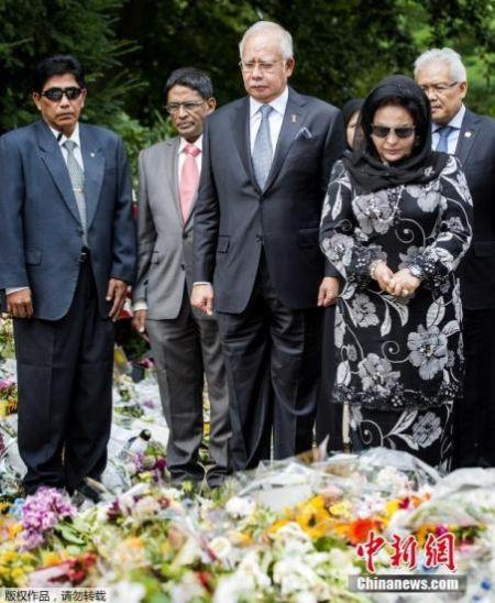 资料图:2014年7月31日,荷兰希尔弗瑟姆,马来西亚总理纳吉布携妻子在当地一处军事基地外献花。法医专家正在该基地内对马航MH17失事航班遇难者的遗体进行辨认和恢复。