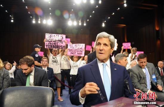 资料图:图为出席听证会的反战人士站在克里身后,高举标语反对美国升级对伊拉克军事行动。中新社发 张蔚然 摄