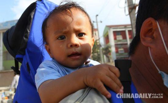 5月12日,在尼泊尔加德满都,一名家长背着孩子转移至安全地带。 据中国地震台网测定,尼泊尔北京时间5月12日15时5分,发生7.5级地震。 新华社发(苏尼尔·夏尔马摄)