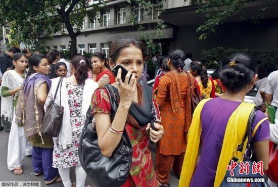 当地时间2015年5月12日,印度阿拉哈巴德,尼泊尔再次发生地震,印度北部民众有明显震感,都立刻跑出建筑物,待在开阔的室外和街道上。图为印度加尔各答民众跑到街上避险,一名女性在向家人报平安。