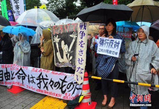 资料图 日本民众冒着大雨持续聚集在国会周边进行抗议活动。中新社发 王健 摄