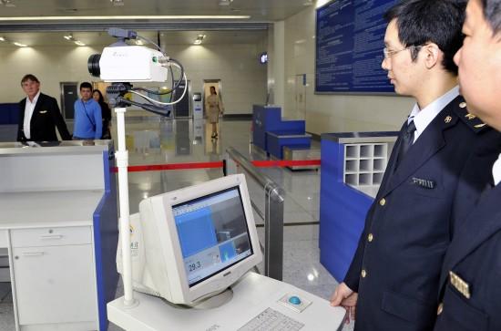 4月30日,检验检疫人员使用红外体温检测仪检测入境旅客体温.