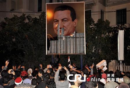 在亚历山大港,示威者们站在一幅被损坏的总统穆巴拉克的画像前。(国际在线/路透)