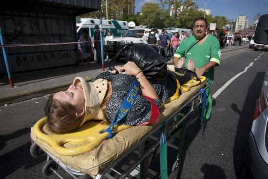 2月22日,在阿根廷首都布宜诺斯艾利斯,阿根廷救援人员运送城铁列车事故中受伤者。