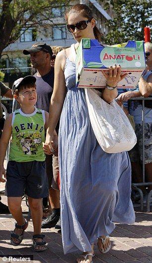 一位妇女带着孩子领取免费派发蔬菜后走在街头