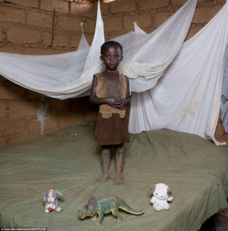 4岁的马拉维孩子只有两个娃娃和一个恐龙模型,她的玩具显得都很破旧不堪。
