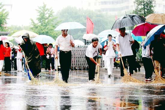 昨天一早,人大附中考点工作人员冒雨清扫积水,保证考生顺利进入考场。本报记者 饶强摄