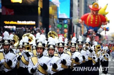 11月26日,参加感恩节游行的队伍从美国纽约时报广场经过。新华社记者申宏摄