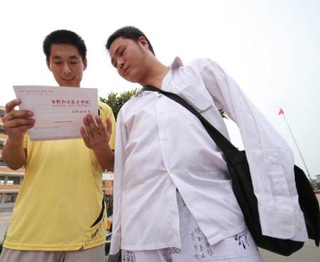 8月23日,无臂男孩戴军颂(右)和同学一起观看刚收到的新生录取通知书。