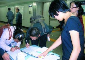 去年,地铁里,非京籍学生家长及志愿者在征集取消高考户籍限制的签名。资料图片