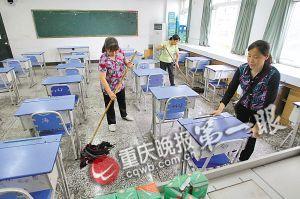 工作人员正在教室打扫卫生,摆放座位,为高考作准备。 重庆晚报记者 杨帆 摄