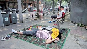 考试开始后,一名考生的表哥铺上地垫,躺在上面休息,等待考试结束