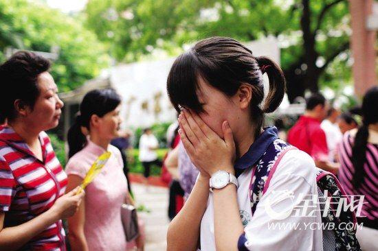 昨日上午,考试结束后,二十一中考点一名女生在家长的翘首以盼中掩面而出。新快报记者 孟祝斌/摄