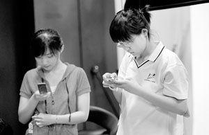 朱竹(右)和同学在发短信 摄/记者郭谦