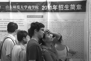 """考生和家长正看各高校招生简章,以使填报做到""""有的放矢"""" 记者 郑涛 摄"""