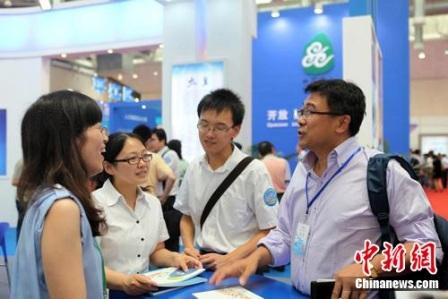 """海外人才在""""2011年苏州国际精英创业周""""上与国内机构工作人员交谈。中新网发 李克祥 摄"""