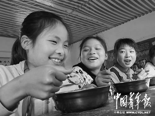 11月21日中午,柳州市融安县大良镇良北小学学生快乐地享用免费午餐,当天午餐的内容是猪肉炒圆白菜和白米饭。本报记者 谢洋摄