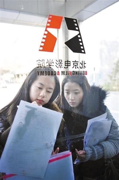 两名报考北电表演系的女学生在玻璃墙外修改报名表。