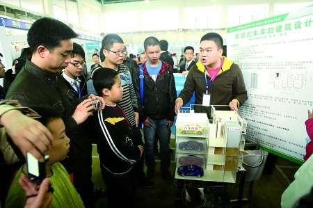 """昨日,参赛选手在向观众介绍""""家居式车库""""时尚建筑模型。 记者 邹飞 摄"""