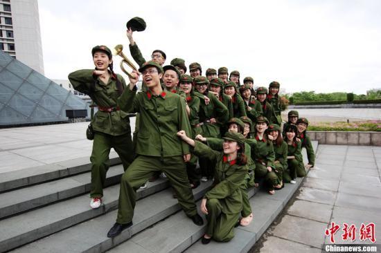 2012年5月9日,浙江工商大学艺术与设计学院毕业生们穿着印有网络流行用语的个性T恤,在学校行政大楼前拍摄另类的主题毕业照。图为身着军装的学生们。 中新社发 浙商 摄