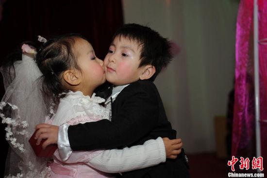 """1月11日,河南郑州一家幼儿园为100多名""""自由恋爱""""的孩子举办了一场""""集体婚礼""""。小""""新郎""""和小""""新娘""""的家长们也在婚礼现场见证。张翼飞 摄 图片来源:CFP视觉中国 2"""