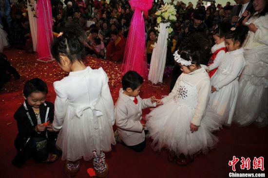 """1月11日,河南郑州一家幼儿园为100多名""""自由恋爱""""的孩子举办了一场""""集体婚礼""""。小""""新郎""""和小""""新娘""""的家长们也在婚礼现场见证。张翼飞 摄 图片来源:CFP视觉中国"""