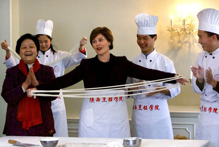 Laura Bush, wife of former US President George W. Bush, tries to make Chinese noodles during a cooking demonstration by chefs at the US Embassy in Beijing Thursday, Feb 21, 2002. 2002年2月21日,美国前总统乔治・华盛顿・布什的妻子劳拉・布什在北京美国大使馆里尝试制作拉面。
