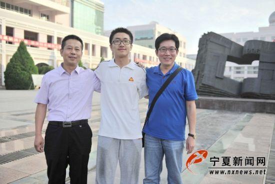2014年高考理科第一名罗政灵(中)和他的父亲(左)以及班主任黄昌彪(右)。