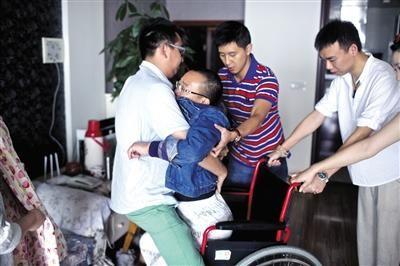 """昨天是中秋节,詹光伟以前的学生来家中看望。他几乎处于""""半瘫痪""""状态,只能让学生将他抱到轮椅上。"""