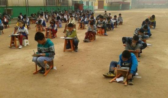 学生在露天操场上蹲着参加考试
