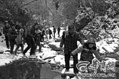 孩子们在家长的陪伴下,小心翼翼地踩着石头过河