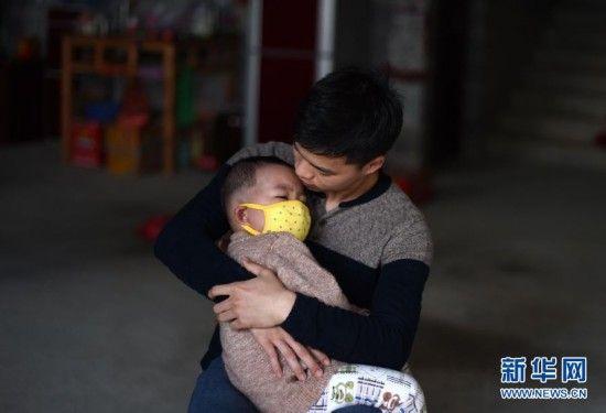 在广西大化瑶族自治县大化镇景山村,韦康仁(右)在哄弟弟韦康虎睡觉(2月22日摄)。新华社记者 黄孝邦 摄