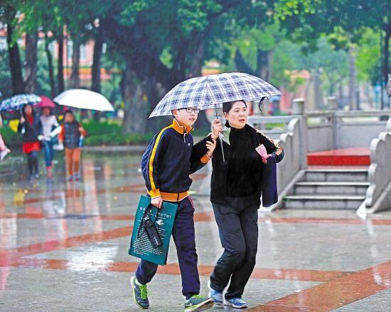 风雨中家长送孩子赶考 羊城晚报记者 陈秋明 摄