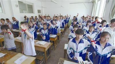 ①距离高考还有一天,甘肃会宁县第一中学的学生手系红色希望丝带为高考加油。