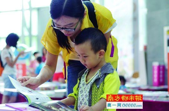 南国书香节惠州书展,一位妈妈在给孩子念书。南都记者 田飞 实习生 林安迪 摄