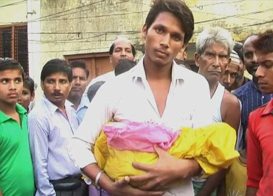 死者的丈夫悲伤地抱着失去头颅的婴儿(网页截图)