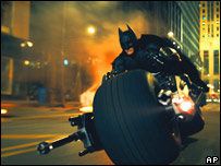 Batman drives his Batbike through Gotham City