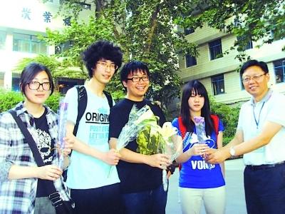 """▲宁海中学郭其俊校长(右一)昨为该校""""解放""""的学生们献花庆祝。王 �Z 摄"""