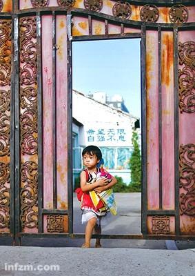 2011年8月16日,北京海淀区东升乡马家沟,一小女孩抱着自己的衣物走出新希望实验幼儿园,这里月底前就会拆除