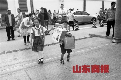 """教师节当天,一名小学生携带礼物""""艰难""""地走着记者郑涛摄"""