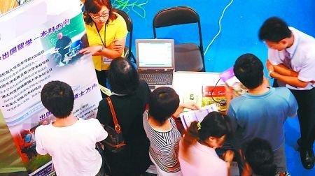 在一国际教育博览会上,学生和家长围在展台前咨询留学情况。 (资料图片)
